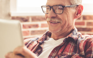 man looking at tablet with smile